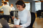 Millennial at desk eating