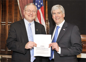 Michigan Gov. Rick Snyder (left) and state Sen. Rick Jones with a copy of the state's new law banning ergonomics regulation.